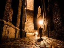 Upplyst lappad gata i gammal stad vid natt Arkivfoton