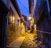 Upplyst lappad gata med ljusa reflexioner på kullersten i gammal historisk stad vid natt Suddigt mörker Fotografering för Bildbyråer
