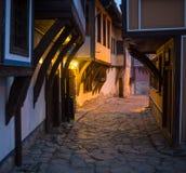 Upplyst lappad gata med ljusa reflexioner på kullersten i gammal historisk stad vid natt Suddigt mörker Royaltyfri Fotografi
