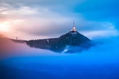 Upplyst skojat sändaretorn och hotell Blå molnig afton i Liberec, Tjeckien royaltyfria bilder