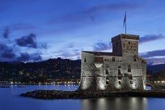 Upplyst slott vid havet i Rapallo Arkivbild