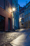 Upplyst smal gata på natten i Tallinn den gamla staden Royaltyfria Bilder