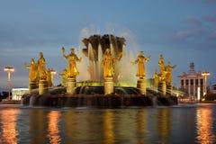 Upplyst springbrunn av kamratskap av folk på skymning Royaltyfri Foto