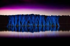 Upplyst symmetri reflekterad på sjön arkivbilder