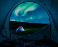 Upplyst tält och morgonrodnad i Island i sommar på natten arkivbild