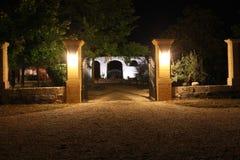 Upplyst trädgårds- borggård på natten Arkivbild
