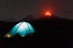 Upplyst turist- tält på natten på bakgrund som får utbrott vulkan arkivbild