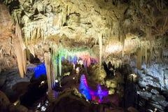 Upplysta stalaktit och stalagmit i den Ngilgi grottan i Yallingup Arkivbild