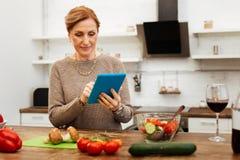 Uppmärksam angenäm dam som blir i kök och bär hennes minnestavla royaltyfria bilder
