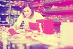 Uppmärksam flickakund som söker efter smakliga sötsaker i supermarket Arkivbild