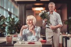 Uppmärksam man som kommer med blommor till en dam royaltyfri foto