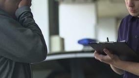 Uppmärksam tjänsteman som talar till det nervösa offret på brottsplats som ner skriver tecken lager videofilmer
