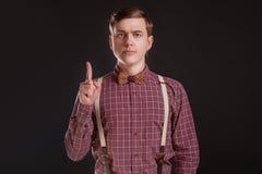 Uppmärksamhet! Strikt stilig ung man i tappningskjortaflugan som håller fingret lyftt och ser kameran, medan stå mot royaltyfria foton