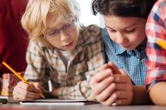 Uppmärksamma nyfikna ungar som läser uppgiften royaltyfri fotografi