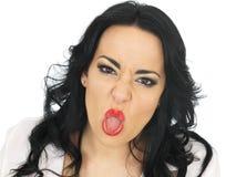 Uppnosig härlig ung latinamerikansk kvinna som drar dumbomframsidor och St arkivfoto