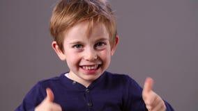 Uppnosig ung förskole- röd hårpojke med fräknar som visar hans spänning med dubbla tummar upp, grå bakgrundsstudio stock video