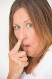 Uppnosigt finger för kvinnanäsplockning Arkivbild
