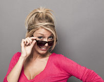 Uppnosigt ungt blont kika över hennes solglasögon Arkivfoton