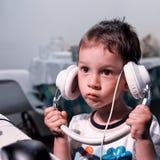Uppochnervänd hörlurarpojke arkivbild