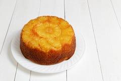 Uppochnervänd kaka för ananas på den vita trätabellen Royaltyfria Bilder