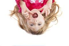 Uppochnervänd liten enfaldig flicka fotografering för bildbyråer