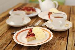 Uppochnervänd plommonpaj med glass och svart te Royaltyfri Foto