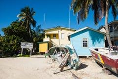 Uppochnervända fartyg och palmträd framme av den Caye Caulkerpolisen arkivfoto