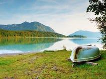 Uppochnervänt fiskeskovelfartyg på banken av fjälläng sjön Morgon höstlig sjö Arkivbilder