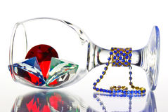 Uppochnervänt med ett exponeringsglas av juvlar på en vit bakgrund. Arkivbilder