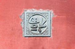Uppochnervänt tecken för kines FU på den röda väggen Arkivfoton
