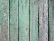 Upprätt randig trävägg, staket, bakgrund med gammal trådsliten grön målarfärg arkivbild