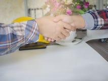 uppröra för affärsmanhänder Bak blommavasen och gulinghjälmen Royaltyfri Fotografi