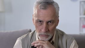 Uppriven äldre man med sammanträde för gå pinne på soffan i rehabiliteringmitt lager videofilmer