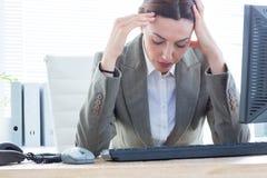 Uppriven affärskvinna med huvudet i händer framme av datoren på kontoret Arkivfoto
