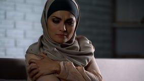 Uppriven arabisk dam i hijab som rymmer den smärtsamma handen, anfall i familj, socialt problem arkivfoto