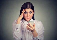 Uppriven chockad allvarlig kvinna som ser hennes mobiltelefon royaltyfria foton