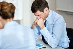 Uppriven eller angelägen affärsman med rapporten på kontoret Royaltyfri Foto