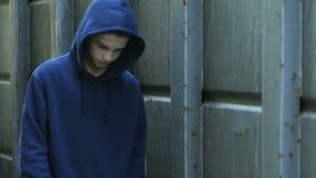 Uppriven ensam pojke som går på skolaträdgården, hoppande over grupper för uttråkad tonåring stock video