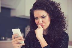 Uppriven förvirrad ung kvinna som ser det läs- textmeddelandet för mobiltelefon royaltyfri fotografi