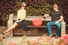 Uppriven flicka på bänk med pojken Arkivfoto