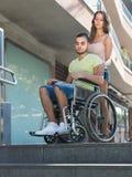 Uppriven fru med mannen i rullstol på trappa Royaltyfri Bild