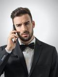 Uppriven ilsken orakad man som talar på telefonen som bort ser Royaltyfri Fotografi