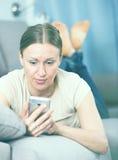 Uppriven kvinna med telefonen arkivbild