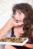Uppriven kvinna som äter choklader i sovrum Arkivbild