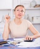 Uppriven kvinna som beräknar finanser arkivbilder