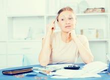 Uppriven kvinna som beräknar finanser arkivbild