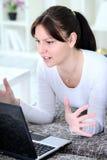 Uppriven kvinna som ser i bärbar dator Arkivfoto
