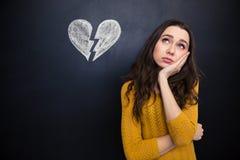 Uppriven kvinna som tänker över svart tavlabakgrund med utdragen bruten hjärta royaltyfri fotografi