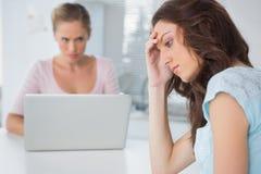 Uppriven kvinna som tänker, medan hennes ilskna vän är stirrig på henne Arkivfoton
