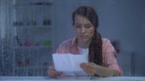 Uppriven kvinnlig läs- bokstav bak regnigt fönster, dåliga nyheter från släktingar stock video
